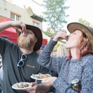 a man and a woman wearing straw hats eat oysters at a Keystone Festival