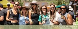 A group of six women wearing sunglasses hold up their wine glasses at a sunny Keystone Wine & Jazz Festival