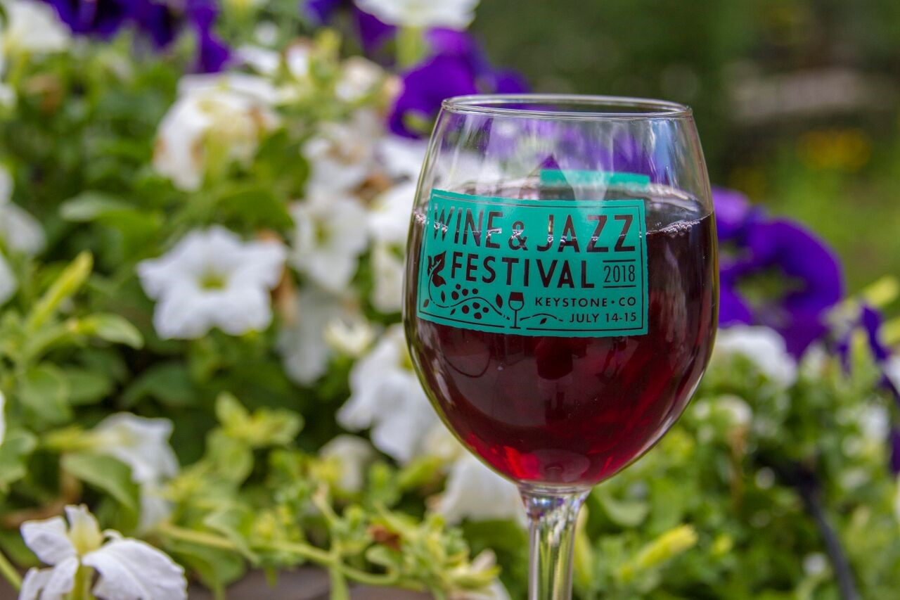 red wine with flowers behind it in keystone co for wine and jazz festival