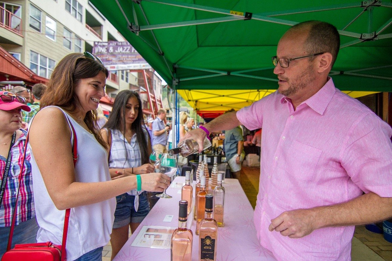 rose wine being poured to smiling woman at keystone wine festival