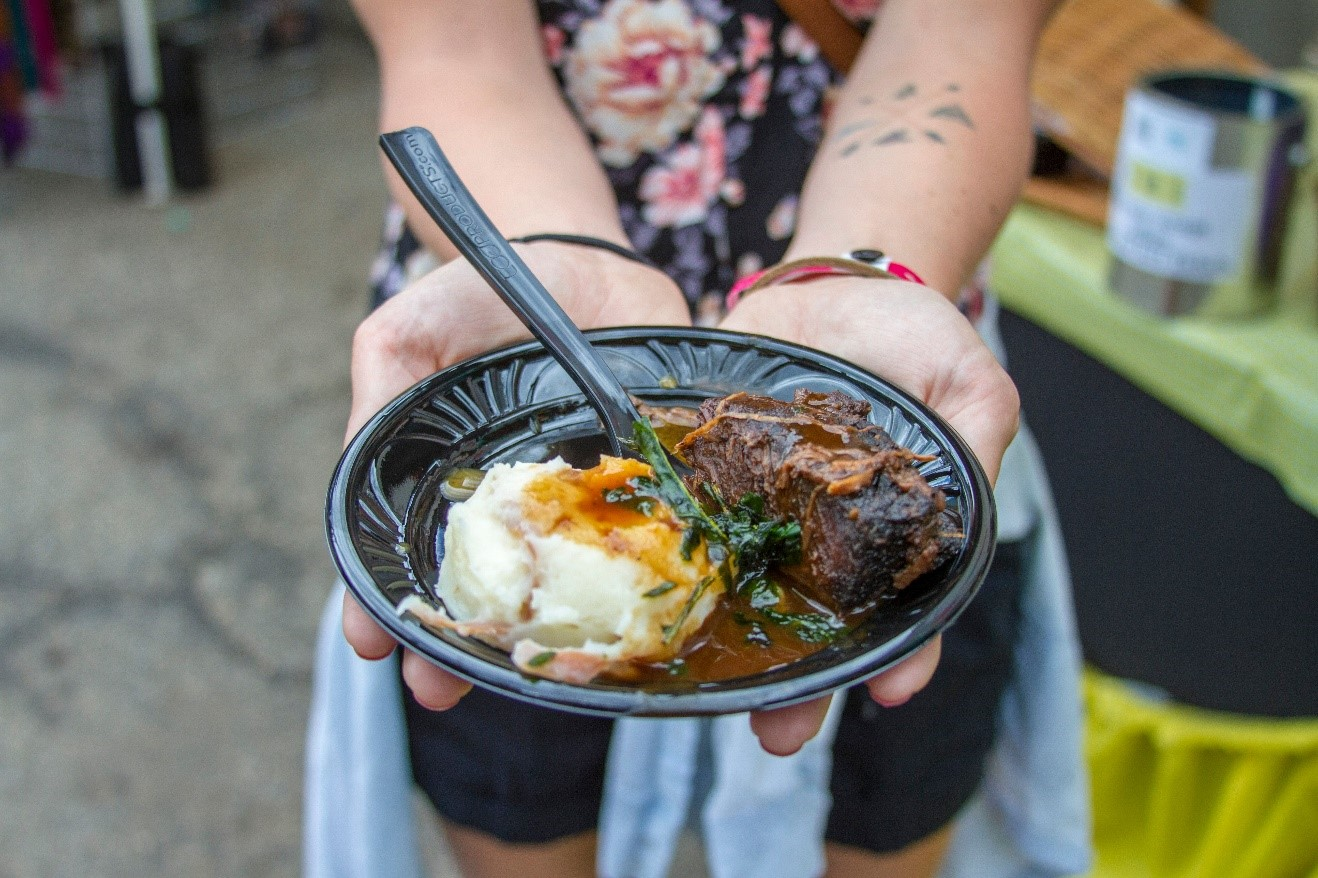 woman holding plate of delicious food at keystone wine and jazz festival