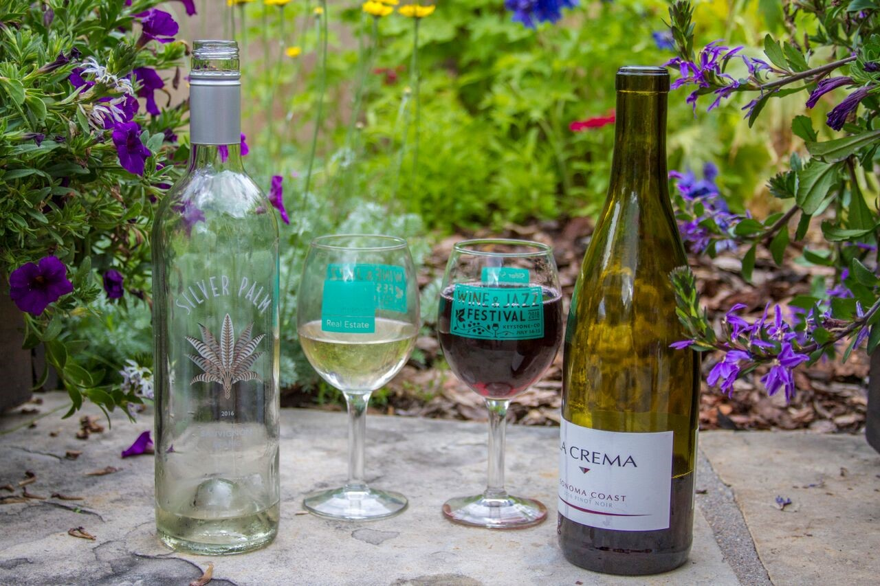 white and red glasses of wine in front of summer flowers